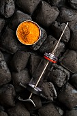 Utensils for barbecued pulled pork: charcoal made of coconut shells, rub and a marinade injector
