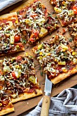 A pizza with pulled pork, sweetcorn, pineapple and onions