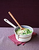 Pea soup in a saucepan with a wooden spoon