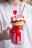 A woman holding a Valentine's freak shake with a mini doughnut and heart-shaped lollipop
