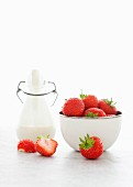 Fresh strawberries and a bottle of cream