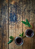 Red wine and laurel leaves on a wooden background