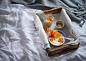 Muesli with yoghurt, citrus fruits and nuts on a tray