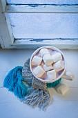 Hot chocolate with marshmallows on a windowsill