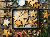 Gingerbread star shaped cookies in wooden tray, sugar powder, nuts, spices, baking molds