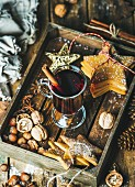 Glass of mulled wine, Christmas decoration toys, gingerbread cookies, nuts, cinnamon, anise and pine cones
