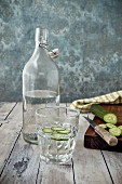 A glass of cucumber water, a bottle of water and fresh cucumber