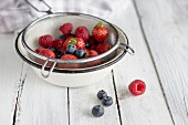 Raspberries, blueberries and strawberries in a sieve