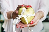 A woman's hands holding a heart-shaped potato