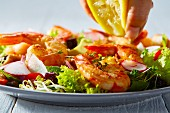Lemon juice being squeezed onto a prawn salad (close-up)