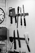 Assorted knives and kitchen utensils on magnetic racks in the kitchen