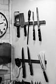 Verschiedene Messer und Küchenutensilien an Magnetleisten in Küche