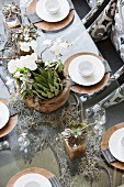 Table elegantly set with white china on wooden chargers and plant arrangement
