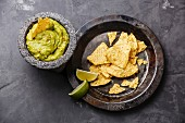 Guacamole with nachos on a grey concrete surface