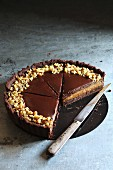 Sliced chocolate and caramel tart topped with walnuts