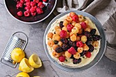 Sponge cake with lemon cream, decorated by fresh colorful yellow red raspberries and dewberries
