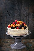 Semi naked cake with lemon cream, decorated by fresh colorful yellow red raspberries, thyme and dewberries
