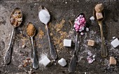 Different vintage spoons with variety of sugar white, brown pink fruit granulated, cubes and crystal
