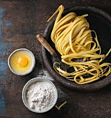 Raw uncooked homemade italian pasta tagliatelle with pasta cutter, bowls with white flour and broken egg