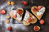 Wafers as heart shape with yellow raspberries, strawberries, sliced figs, ricotta cheese and sugar powder