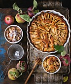 Apple cake in a white ceramic flan dish with fresh apples, honey and cinnamon sticks