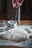 Unbaked wholemeal bread being dusted with flour