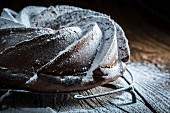 Dark chocolate cake dusted with icing sugar on a wooden table