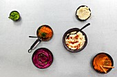 Six different vegetable purées in bowls