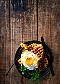 A fried egg on savoury waffles with dried tomatoes, Halloumi and thyme