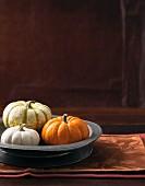 An arrangement of three decorative pumpkins in a grey metal dish