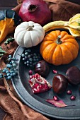 An autumnal arrangement of pumpkins, chestnuts, pomegranates and berries