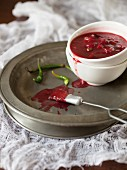 Hot plum sauce with chilli in a bowl on a metal plate
