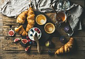 Breakfast with croissants, ricotta, figs, berries, honey and espresso on a wooden surface