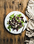 Arugula, beetroot, feta cheese and sunflower seed salad in white ceramic plate