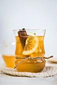 Apple cider with a cinnamon stick, lemon, honey and apple vinegar