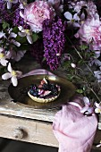 A fig and blackberry tartlet on a wooden table with flowers