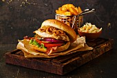 A burger with chicken breast and fried onions served with coleslaw and potato wedges