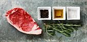 Rohes Rindersteak mit Rosmarin, Pfeffer, Öl und Salz