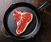 Raw fresh meat T-bone steak on cast iron frying pan on wooden background