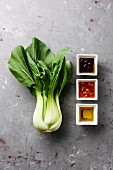 Fresh Pak choi cabbage and different sauces on gray concrete stone background