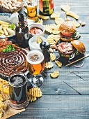 Beers assortment, grilled sausages, burgers, fried potato, corn, chips and sauces on dark wooden background
