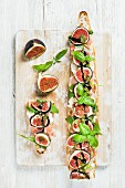 A baguette topped with ham, mozzarella, rocket, figs and basil on a wooden surface