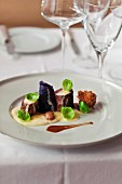 Venison loin served with red cabbage, chestnuts Brussels sprouts and cauliflower puree