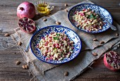Couscous with chickpeas, almonds and pomegranate seeds on blue ceramic plates
