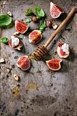 Aufgeschnittene Feigen mit Ricotta, Basilikumblätter, Haselnuss und Honig