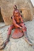 Himba woman applying plant balm to skin
