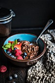 A bowl of chocolate porridge with berries and honey