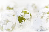 Balls of raw biscuit dough with matcha and white chocolate rolled in icing sugar