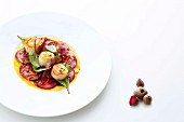 Scallops on a bed of beetroot carpaccio with spiced orange butter