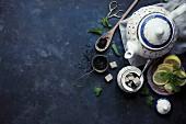 Teeblätter, Teekanne, Zitronenscheiben und Zucker